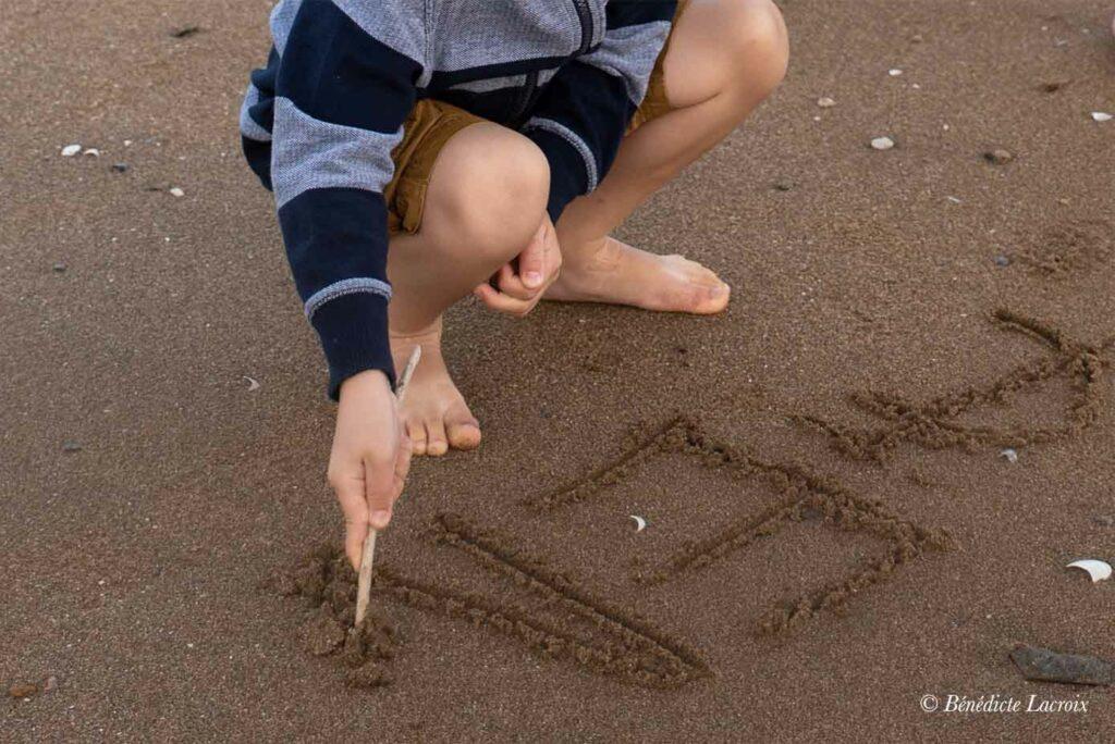 enfant ecrit son nom dans le sable