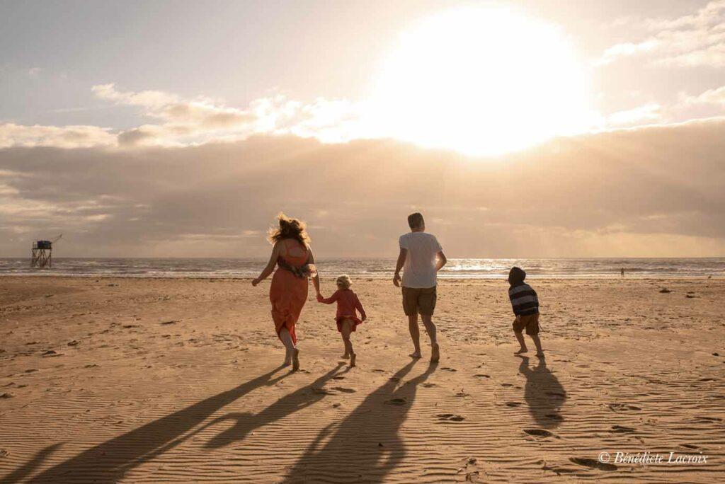 famille marche sur la plage contre jour