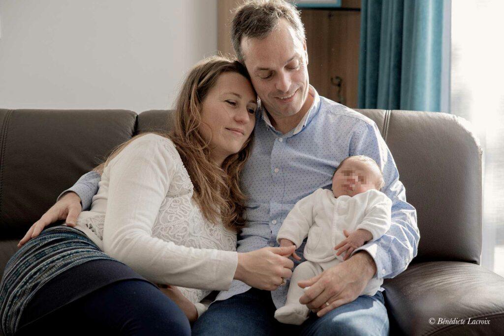 bebe dans les bras de ses parents